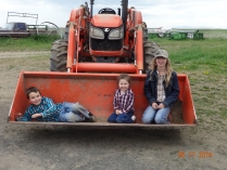 Ronnie, Katie and Julie riding in the tractor bucket.